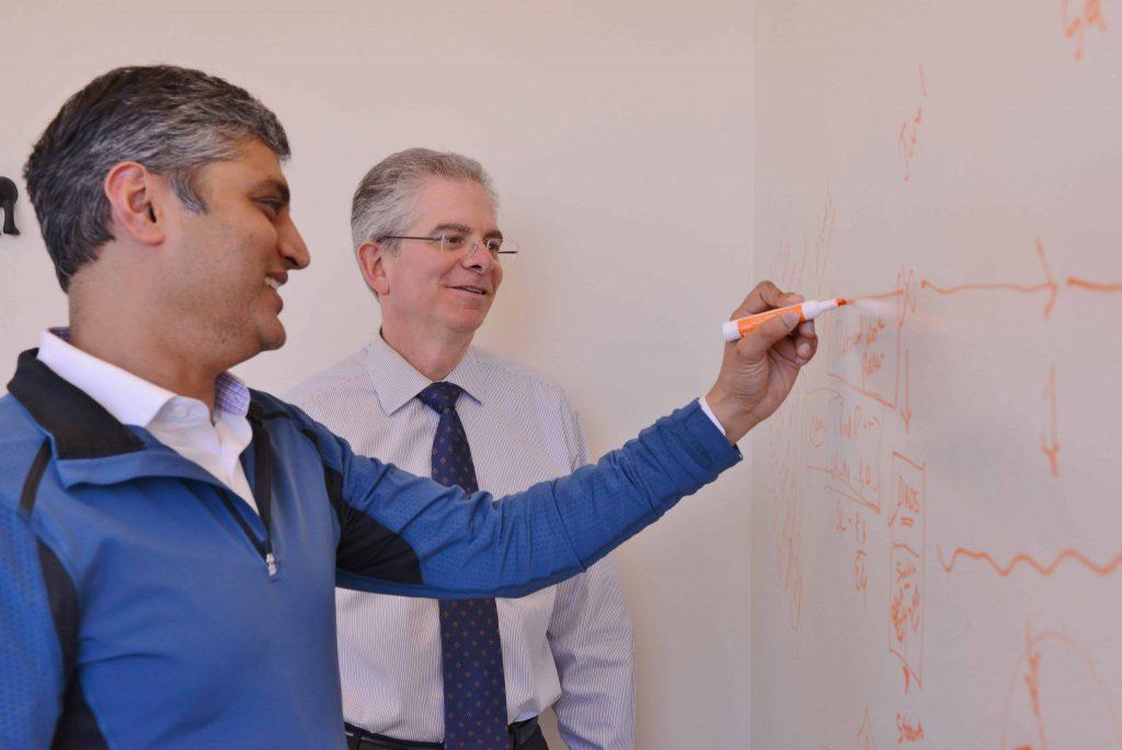 John Ayanian looking on as Brahmajee Nallamothu writes on a white board.